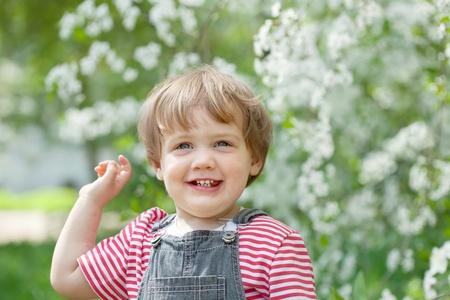 Happy toddler at  blossoming garden in spring photo
