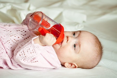 babygro: Baby girl of 5 months with sippy cup on white blanket