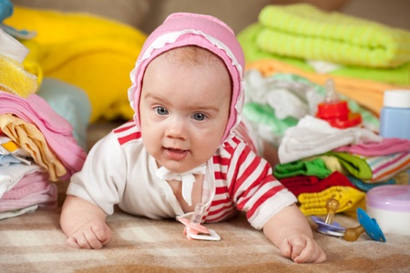 babygro: Baby girl with heap of babys wear laying on checked blanket
