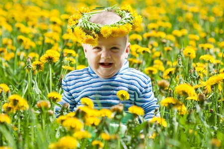 chaplet: happy baby in flowers chaplet at meadow Stock Photo