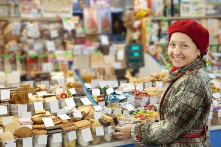 Mature woman chooses sweets at shop photo