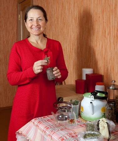concoct: Mature woman brews herbs in a teapot at home kitchen