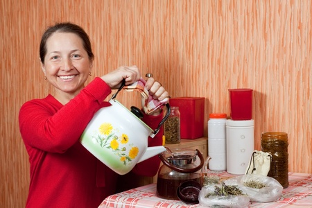 Mature woman brews herbs in a teapot at home kitchen Stock Photo - 13586821