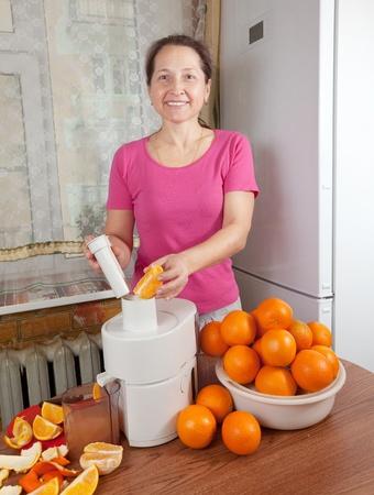 liquidizer:  Mature woman making fresh orange juice in her kitchen  Stock Photo