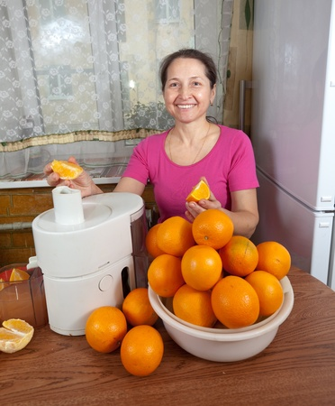 Mature woman making fresh orange juice in her kitchen photo