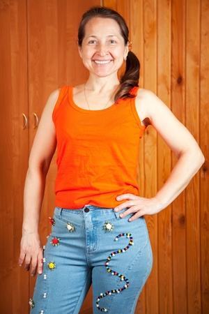 Mature woman  shows a handmade jeans beaded by herself Stock Photo - 13586788
