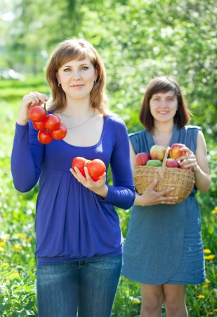 Happy young women with apple harvest in orchard photo
