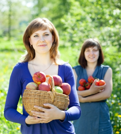 Happy girls with apples harvest in garden photo