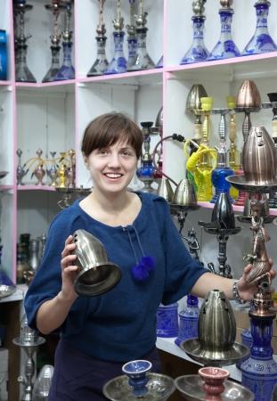waterpipe: Mujer turista elige sheesha en la tienda de egipcio