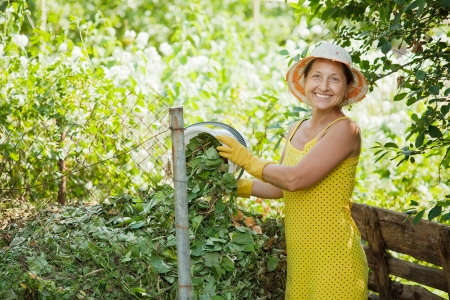 composting: Female gardener composting grass in garden Stock Photo