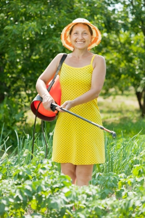 insecticidal: Mature woman spraying vegetables plant in field