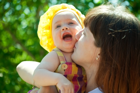 Happy mother with baby daughter  against nature photo