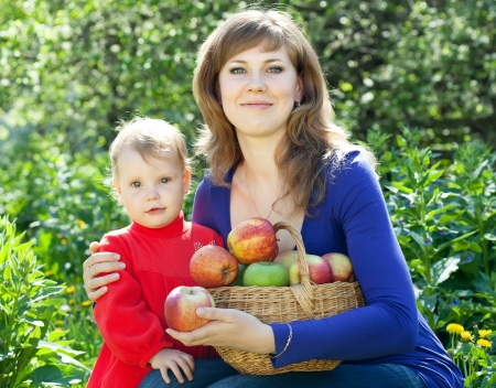 Happy woman and child  women with basket of harvested apples in garden Stock Photo - 13658695