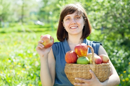 Happy young woman with apple harvest in orchard photo