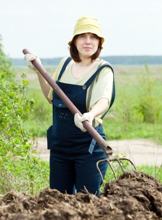 muck: Woman works with animal manure at field Stock Photo