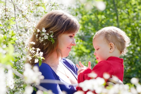 Happy mother and baby daughter in blossoming garden photo