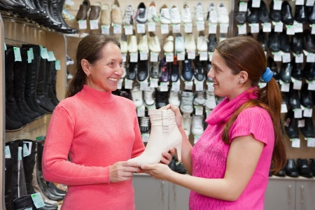 Two women chooses shoes at shoes shop photo