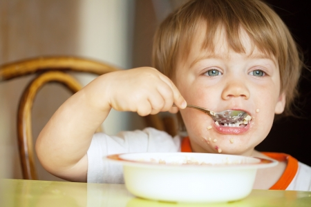 two-year child himself eats cereal with a spoon photo
