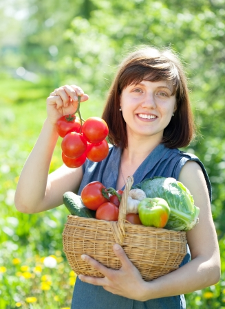 Happy young woman with basket of harvested vegetables in garden Stock Photo - 13750128