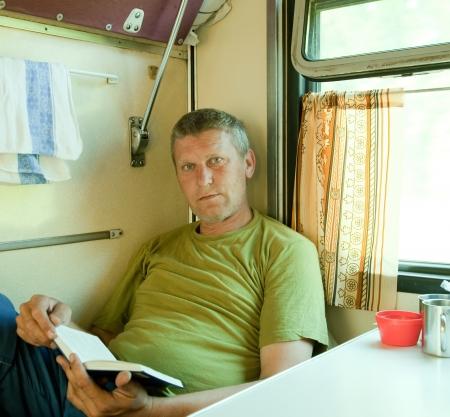 Hombre maduro libro de lectura en el tren coche-cama
