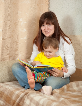 mother and daughter reading book in home photo