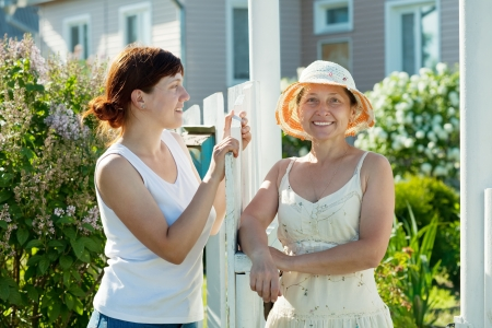 Two happy women near fence wicket  in front of home Stock Photo - 13801749