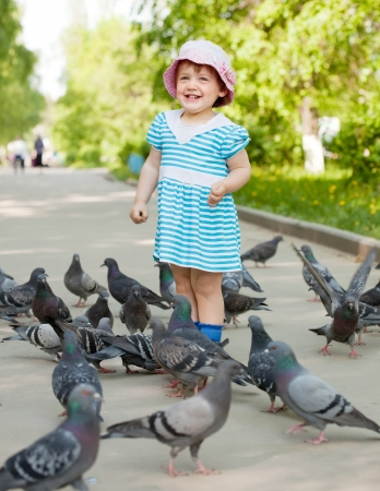 Happy two-year girl feeding doves  in the city street Stock Photo - 13822566