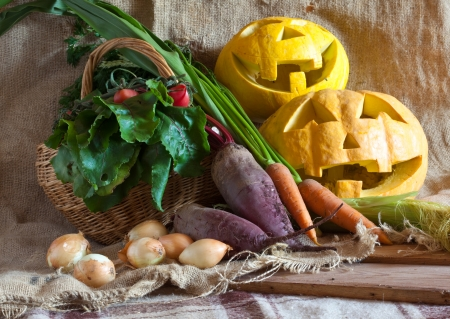 Halloween pumpkin and harvested vegetables on sacking photo