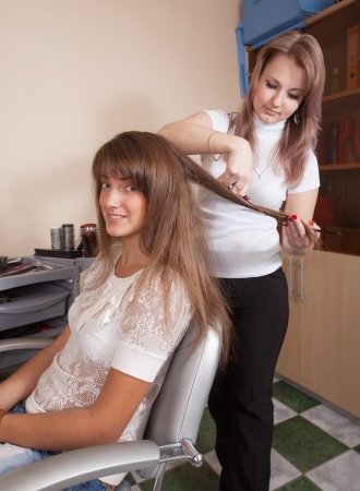 haircutting: Female hair stylist working with long-haired girl Stock Photo