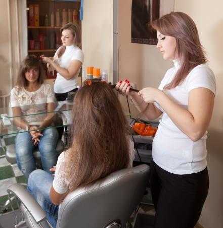 Female hairdresser works on woman hair in salon photo
