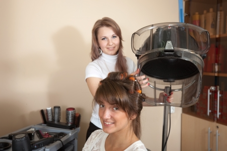 Female hairdresser working with hair dryer. Focus on customer photo