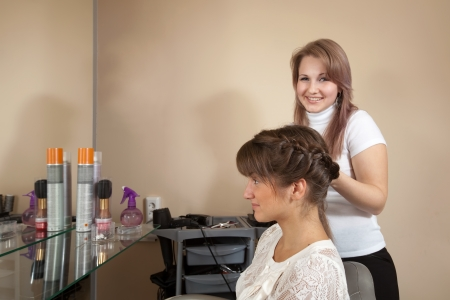 Female hair stylist working with long-haired girl. Focus on customer photo