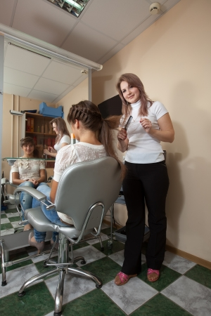 Female hair stylist working with long-haired girl Stock Photo