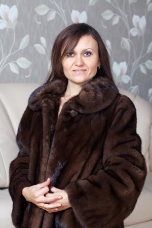 bontjas: Portret van vrouw in bontjas thuis interieur Stockfoto