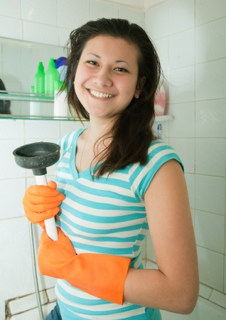 Young woman with plunger in her bathroom photo