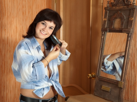 Girl combing her long hair in home interior Stock Photo - 13902573