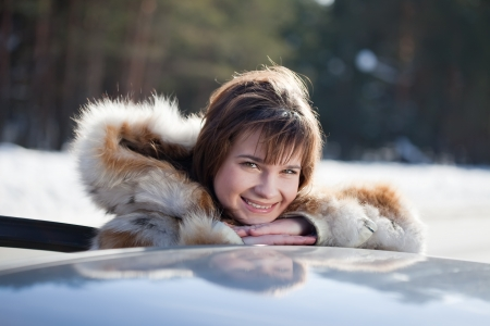 capping: Portrait of  happy woman near her car in winter road