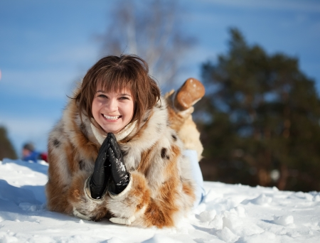 Happy girl lying down on the snow in winter photo