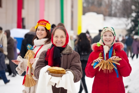 sudarium: women in russian traditional clothes with pancake and round cracknel during  Shrovetide