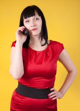 Woman in red dress speak by phone over   yellow background photo