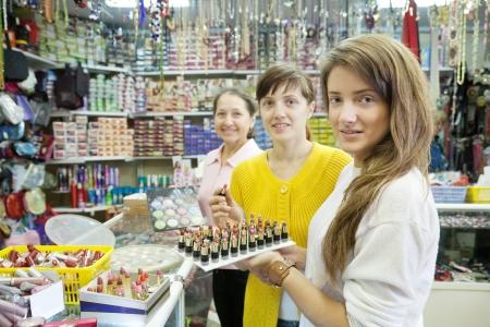 women chooses   lipstick at cosmetics  shop photo
