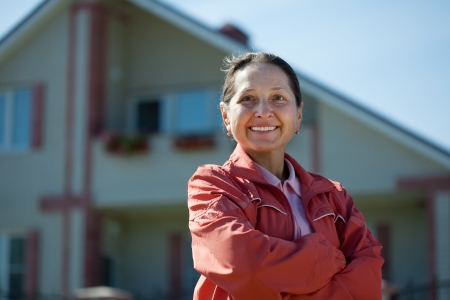 Outdoor portrait of mature woman against real estate photo