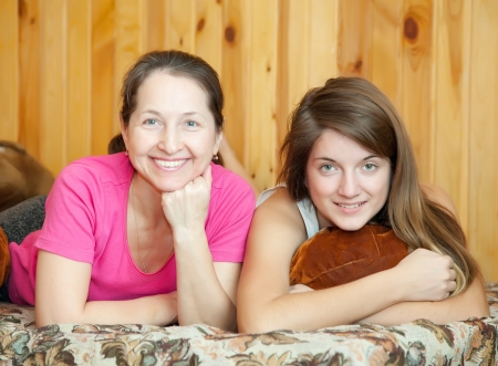 teenr daughter and mother laying on sofa at home photo
