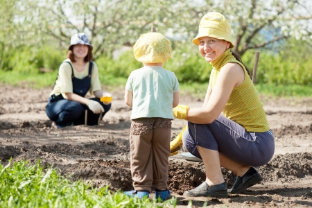 sows: women and kid sows seeds in soil at field