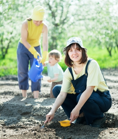 Happy women with child works at garden in spring photo
