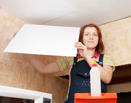 Young woman glues ceiling tile at home Stock Photo - 13982412