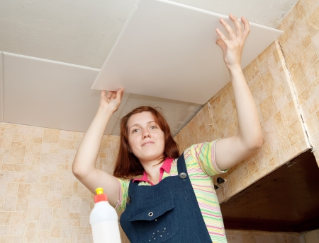 Girl glues ceiling tile at home Stock Photo - 13982440