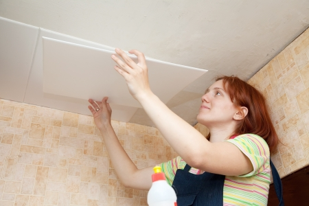 Girl glues ceiling tile at home Stock Photo - 13982434