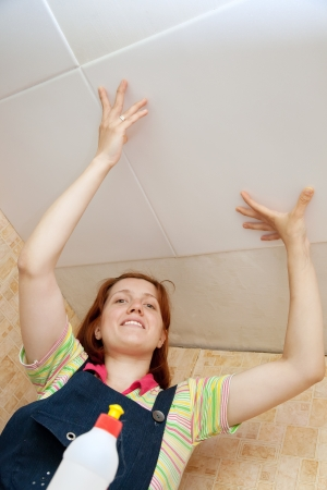 remount: Woman glues ceiling tile at home