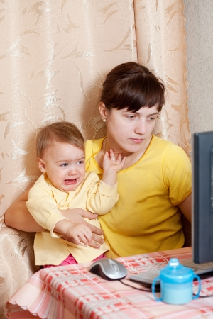 Woman with crying baby working  with computer at home photo